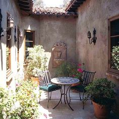 Create Old-World Style with Sconces - Wrought-iron sconces bring a touch of Tuscany to this sliver of an outdoor room. Choosing light fixtures with the same finish as the door pulls, fencing, and outdoor furniture gives your outdoor rooms a professional,