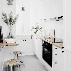 Black appliances, white cabinets, wood counter