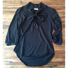 New York & Co Black 3/4 Top with bow detail This top is adorable with it's tie detail in the front and gold accent buttons on the sleeves. It is a blousy silky material – the tag says it is 100% polyester. Size small but would easily fit a medium. New York & Company Tops Blouses