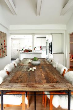 This all-white dining room features a reclaimed wood dining table and easy access to the kitchen. White faux fur covers wood dining chairs along the dining table, while modern wall art adds a touch of color to the space.