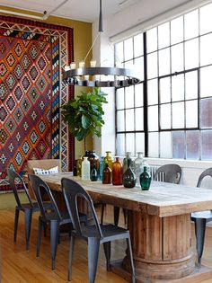 A wall-hung tribal rug and clutch of rainbow-hue glassware add an infusion of color. Industrial lighting, a chunky table and metal chairs supply the necessary cool quotient. | Design: Sarah Richardson