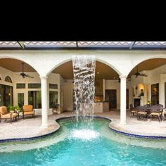 Awesome backyard with a waterfall flowing from the house to the pool!!!