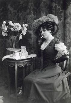 Ladies' fashion. Studio portrait of a smoking woman, dressed in a gown with a lace low neckline, and wearing a hat with ostrich feathers.[Paris, France, early 20th century]