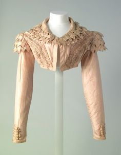 Pink silk spencer with front opening and turn down collar, applied decoration of pink satin rouleaux loops with 5 rouleaux strips at wrist and 2 rows at lower edge, collar piped in silk, 3 layers of `leaf' decoration on epaulettes over straight sleeves; c.1815. Chertsey Museum