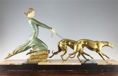 A French Art Deco patinated metal figure group of a young maiden, with two hounds on a black marble and brown onyx rectangular base, signed Menneville
