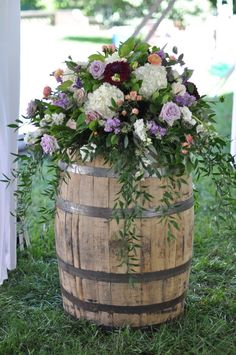 wedding barrel arrangement with a touch of purple, coral and burgundy - a perfect welcome for your guests! Whiskey Barrel Flowers, Whiskey Barrel Decor, Whiskey Barrel Wedding, Wine Barrel Flower Arrangements, Wedding Flower Arrangements, Floral Arrangements, Wedding Hall Decorations, Wedding Centerpieces, Floral Wedding