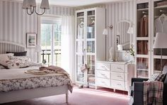 Traditional bedroom with grey and white striped wallpaper, pink floor and white wardrobes with glass.