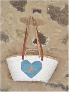 Capazo pintado de color blanco con asas de cuero de 70 cm y corazón de lentejuelas de color azul turquesa con una estrellita de color beige. Medidas 40x25x20 cm
