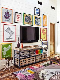 Colorful maps and posters surround the TV in the living area to create a functional art display. The media stand, though it bears the same vintage character as other pieces in the house, is actually new and mixes metal and worn-looking wood for an industrial look.