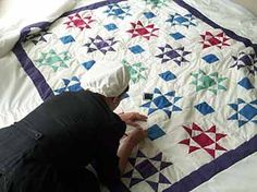 An Amish woman, quilting.