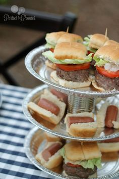 We love a three-tiered lazy susan for displaying Labor Day yummy snacks! Mini hamburgers and hotdogs, picnic, bbq, blue and white checkered cloth