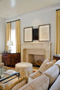 Sliding prints hide the TV above a fireplace. #decortip