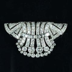 A diamond double-clip/brooch, circa 1930,  decorated at the centre with a stylised cascade of brilliant-cut diamonds with raised channel-set diamond detail, the pleated shoulders similarly set, diamonds approximately 5.00 carats total, length 5.5cm.