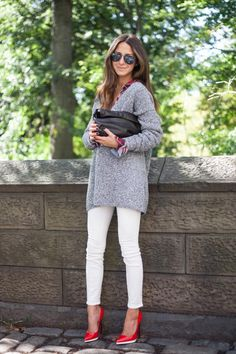 Arielle Nachami is wearing a red shoes from Christian Louboutin, jeans from AYR, plaid button down shirt from Rails, oversized heavy knit sweater from NastyGal, sunglasses from Ray Ban and the clutch is from Marie Turnor