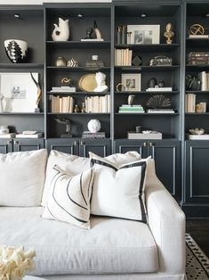 Shannon Claire black built-ins, white sofa, custom art, family room
