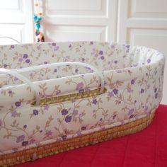 Funda moises con algodón estampado en tonos lilas, malvas, grises y crudo con relleno guateado. Funda válida para moisés con base 78x37 cm. Alto: 21 cm. y apertura para el asa de 19 cm.