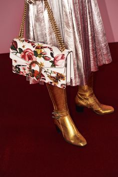 The Gucci Garden Dionysus bag and pleated metallic silver leather skirt. Mid-heel knee boots in metallic gold leather and textured tiger head closure encrusted with crystals.