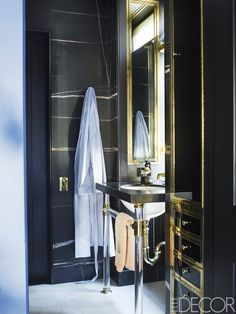 A sink from Urban Archaeology, with fittings by Waterworks, in Alexander's bath; the cabinets are black glass with brass trim, the walls are clad in Saint Laurent marble, and the flooring is limestone. - ELLEDecor.com