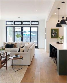 modern farmhouse living room decor, neutral living room design with white walls and modern meets traditional furniture, tv cabinet, modern gray sofa with neutral throw pillows and artwork with neutral area rug and coffee table decor open floor plan into modern kitchen with black kitchen island