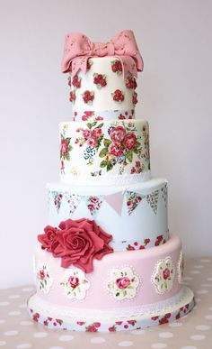 Four-tiered wedding cake with lots to love. Hand-painted flowers, sugar paste work, and a big fondant bow on top with little sugar paste flowers on it. No detail is spared on this vintage-look cake.