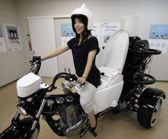 "Japanese toilet maker TOTO employee Akiko Matsuyama gets on a ""Toilet Bike Neo"" displayed at its showroom in Fujisawa, near Tokyo, Thursday,..."