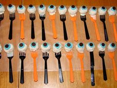 """eyeball cake pops served on forks. This would be so fun for a Halloween party / family get together! they'd even be great as centerpieces if they were all set up standing inside a """"potion"""" bottle or cauldron... hehe too fun!"""