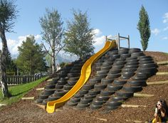 Curved slide on a slope with tire steps on wood chips