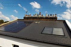 Photovoltaic roof panels and thermal solar panels on roof of Victorian house Camden Town London UK