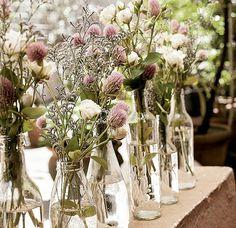 Uma mesa bonita não pede, necessariamente, vasos caros e cheios de pompa. Com um conjunto de garrafas e belas flores, você resolve a decoração do jantar e ainda arruma uma boa desculpa para abrir um vinho novo
