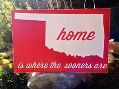 Home is where the Sooners are is a custom wood typography word art sign. It is hand painted with a red background with red/white lettering