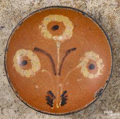Pennsylvania redware pie plate, 19th c., with three yellow slip flowers, 6 3/4'' dia. - Price Estimate: $500 - $1000