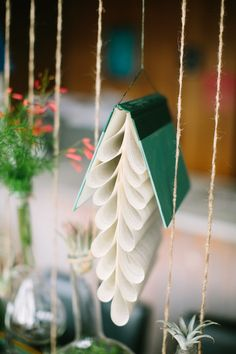 Folded book pages hanging among flowers for a unique centerpiece