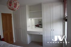 dressing table and floating shelves between two wardrobes