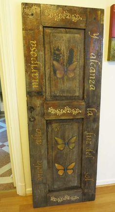 Puerta antigua pintada con mariposas y una leyenda en dorado. Textura en relieve con arena.