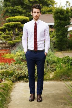 crisp white shirt. skinny tie. blue trousers. brown belt and shoes.