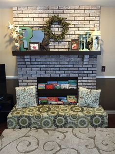 Baby proofed fireplace created with foam bench over the hearth and bookcase insert