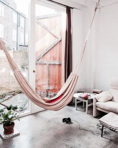 A hammock is the perfect place to recline and relax. Install an indoor hammock for beachy relaxation all year long. For more indoor hammock design ideas, visit domino. My Living Room, Home And Living, Living Spaces, Kitchen Living, Room Kitchen, Modern Living, Interior Architecture, Interior And Exterior, Indoor Hammock