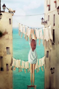 Young girl hanging clothes on a washing line in a european town with cat on roof top  COPYRIGHT:Marta Orlowska