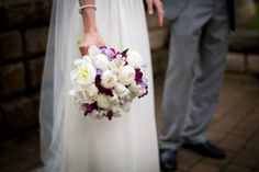 either this kind of bouquet, with a little hint of purple or one that is all purple and then the bridesmaids would have all white against purple dresses with cowboy boots!