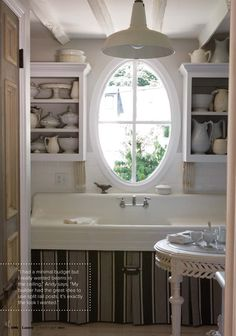 A huge, skirted utility sink spans the width of this modest kitchen setting a French-cottage vibe.