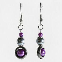 Boucles d'oreilles pendantes créées avec des perles en verre nacrées violettes et anthracite, des perles hématites, et des éléments en inox. Par Naïas.