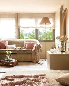 17_Salón en tonos beige con sofá, lámpara de pie, cortinas, plaid y cojines de…