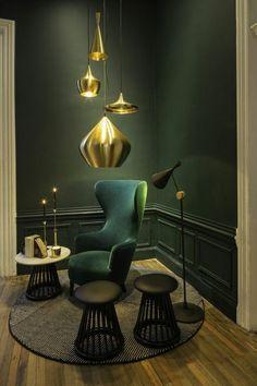 lampe en or tapis rond chaise en bleu foncé sol en parquet mur vert eclairage intérieur