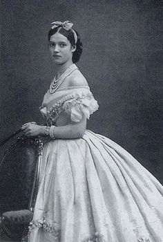 Young lady from the 1850's-60's wearing a ballgown, beautiful pearls and a bow in her hair.