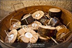 cute wedding favors cut logs with candle inside tied with raffia and presented in an apple basket! #rusticweddingdecorations