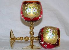 """This is a picture of two of the five Bohemian ruby glass claret wine glasses I had. Each has a twisted stem with gold encrusted hand painted and enameled floral and leaf pattern. Each stands 5-1/2"""" tall and hold 5 ounces. Could be Moser but is in the Moser style."""