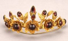 Dating to about 1850, this beautiful gold tiara is set with round and leaf-shaped cabochon garnets in the form of a half-circlet of flowers and foliage. Made in England, the tiara shows the sort of requisite ornament worn by aristocratic English ladies at important functions. Similarly, it's wholly demonstrative of the jewelry designs of the 1850s—designs which relied on natural ornament and motifs based on the beauty of the English garden