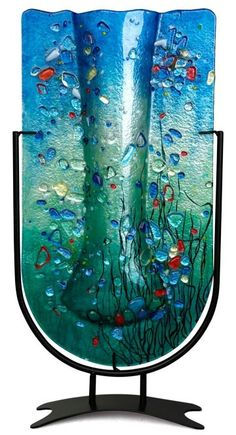 Marine colors are featured in this 18.5x10 inch tall U-shaped fused glass vase with aqua blue and green, along with many other colored pieces fused in place. Stand included This elegant, handmade, fus