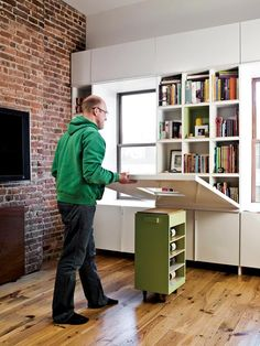 """Folding table with a rolling pedestal instead of legs.  Designed by """"noroof.""""  How awesome would this be as a craft / project area! Put craft supplies on the shelves, fold down table for crafts when needed, then pack everything away out of sight the rest of the time!"""