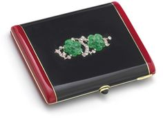An Art deco diamond, jade and enamel box The hinged box of rectangular form, the black enamel ground with red coral enamel border set to the centre with rose-cut diamond and carved jade stylised oriental blossom motif, to a sugarloaf sapphire thumbpiece, width 7.8 cm, French assay marks.